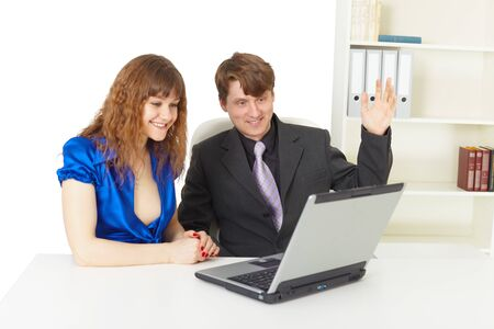 emotionality: Man and woman are happy looking at a laptop screen in office