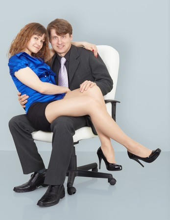 Young woman sitting on the lap of a man sitting in a chair photo