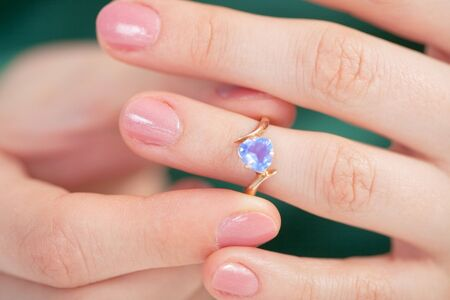 try: The Golden Ring with a dark blue jewel try on a finger Stock Photo