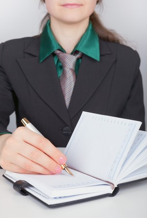 The business woman writes down plans in a notebook photo
