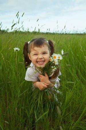 flores peque�as: El ni�o alegre abraza flores silvestres en el campo  Foto de archivo