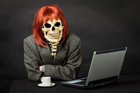 A man dressed as death sits at a table with a computer photo