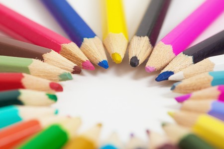 Several childrens colored pencils arranged in a circle photo