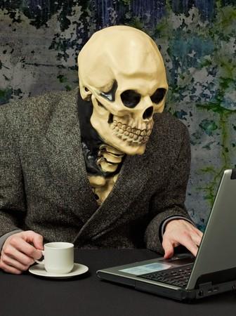 esqueleto: La persona terrible - un esqueleto utiliza Internet  Foto de archivo