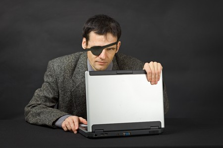 trickster: The computer pirate look with one eye on dark background