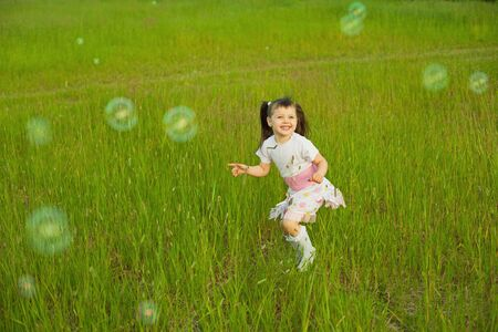 The happy little girl among soap bubbles on field photo