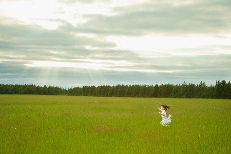The little girl in a dress runs on a meadow