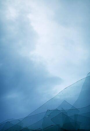 The blue cloudy sky through the broken window photo