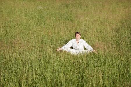 meditates: The man in a kimono meditates sitting in a grass