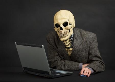 creepy monster: Lo scheletro terribile in una tuta siede presso ufficio nero con il portatile