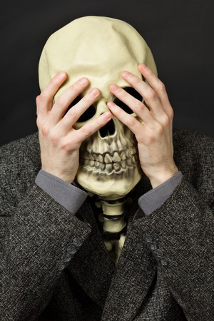 Skeleton covering his eyes on a dark background photo