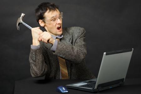 reparaturen: Der w�tende junge Mann bricht einen Hammer computer
