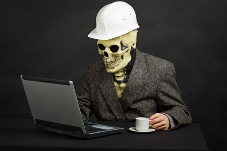 The comical construction superintendent in a helmet and a skeleton mask works with the computer photo