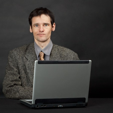 Funny young man sitting at a table with a computer Stock Photo - 7604236