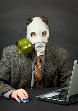 The amusing person has dressed a gas mask and works with the computer photo
