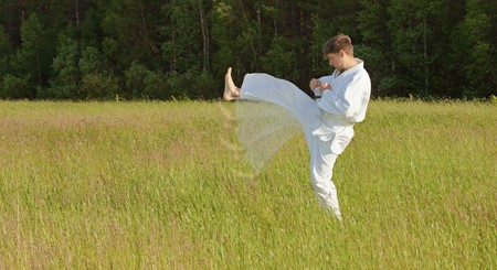 The man in a kimono fulfills blows by feet in the field Stock Photo - 7610230