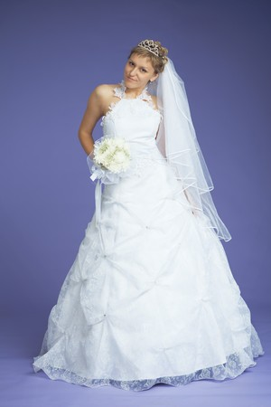 The beautiful bride in a white dress poses on a violet background photo