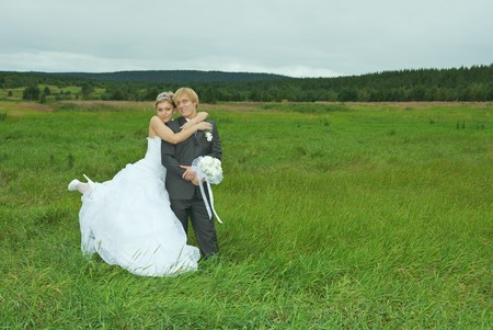 The bride and groom embrace on a green field