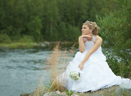 The sad bride sits on river bank and looks afar Stock Photo - 7610245