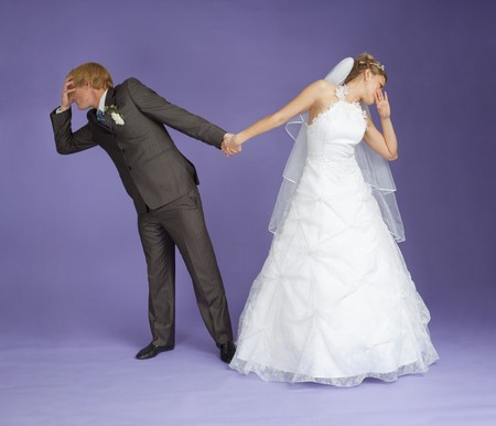 Comical emotional groom and the bride holding hands on violet background photo
