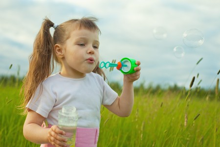 The little girl starts soap bubbles in the field photo