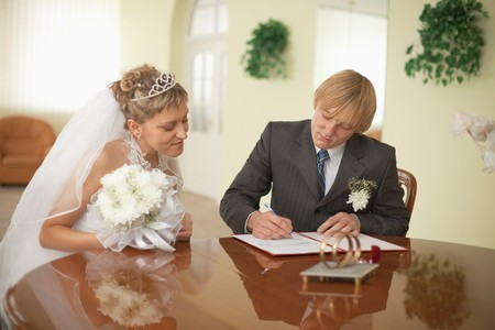 The groom and the bride at the moment of solemn registration of marriage
