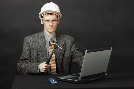 The man in a helmet with a hammer was going to repair the computer photo