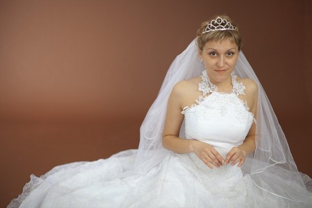 The beautiful amusing bride in a white dress sits on a brown background photo
