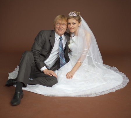 Happy newly-married couple sits on a brown background photo