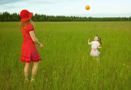Mum and daughter play with a ball in the field Stock Photo