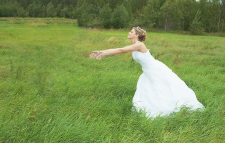 The bride hastens towards to the groom on a green meadow