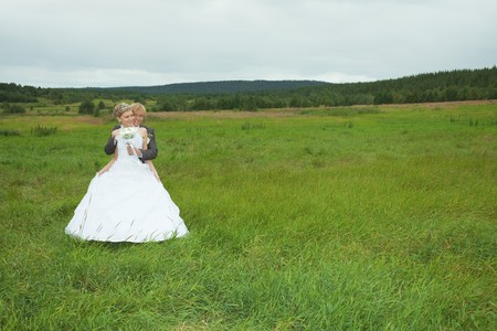 The groom embraces the favorite bride in a green field