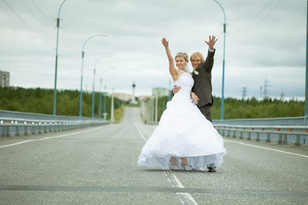 Newly married have fun standing on country highway