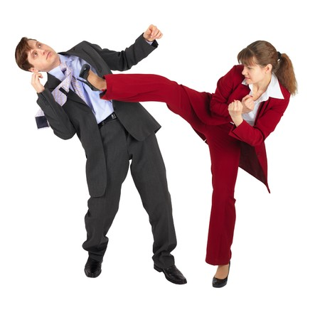 The young woman kicks the man in a business suit photo