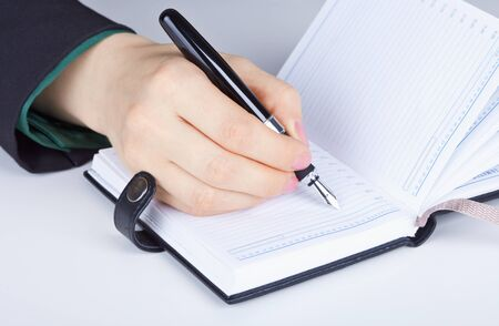 The womens hand and writes in diary photo