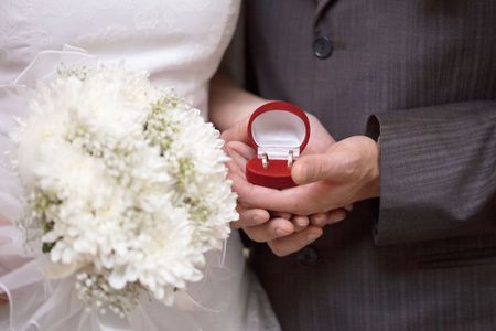 Wedding rings in the hands of newlyweds close up photo