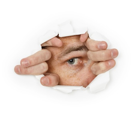 A man looks through a hole in the paper photo