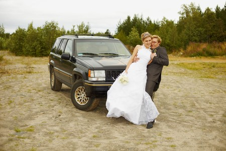 Newly married go to a honeymoon trip by the car