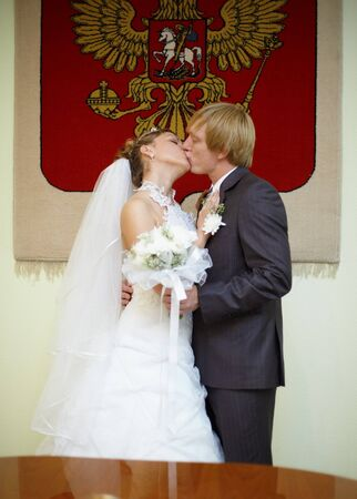 Newly married kiss at wedding ceremony under Russian arms photo