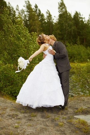 The groom passionately kisses the bride among a grass and trees photo