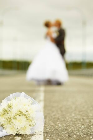 Newly married kiss in the middle of highway photo