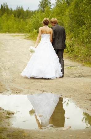 marriageable: Newly-married couple walks on rural road after a rain Stock Photo