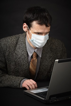 A man in a medical mask diagnoses computer Stock Photo - 7955159