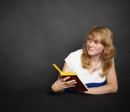 The amusing girl with the book in a dark room Stock Photo - 7955171