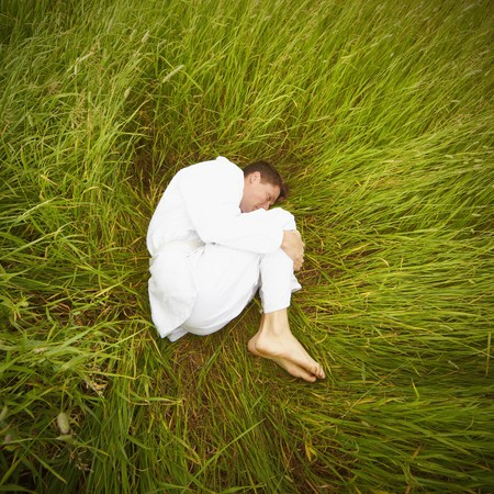 A man lying in the grass in the fetal position photo