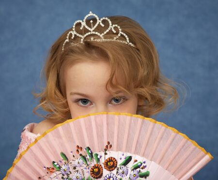 Portrait of a young girl with an Oriental fan in the hands photo