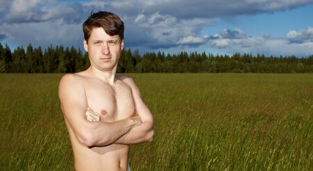 Naked young man on a background of green field Stock Photo - 8028416