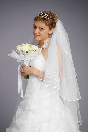 Formal portrait of beautiful bride on a gray background photo