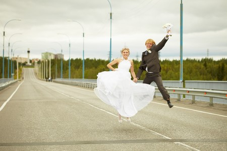 Newly married young pair cheerfully jumps on highway photo