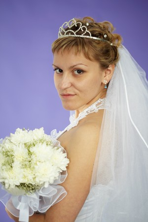 The bride looks at us - a portrait on a purple background photo